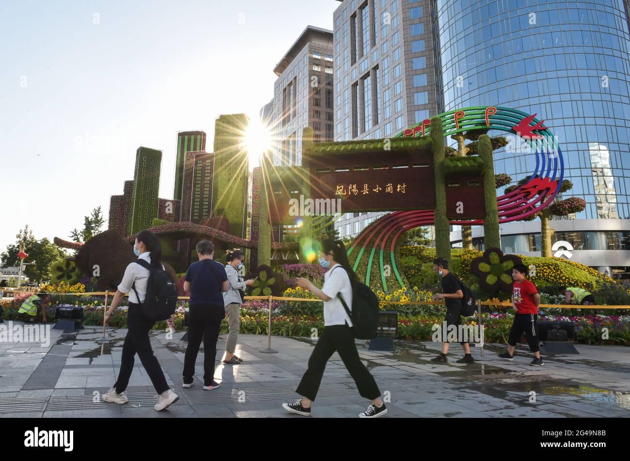 Pékin, Chine. 19 juin 2021. Les gens marchent devant des décorations florales établies le long de l'avenue Chang'an à Beijing, capitale de la Chine, le 19 juin 2021. Credit: Chen Zhonghao/Xinhua/Alay Live News Banque D'Images