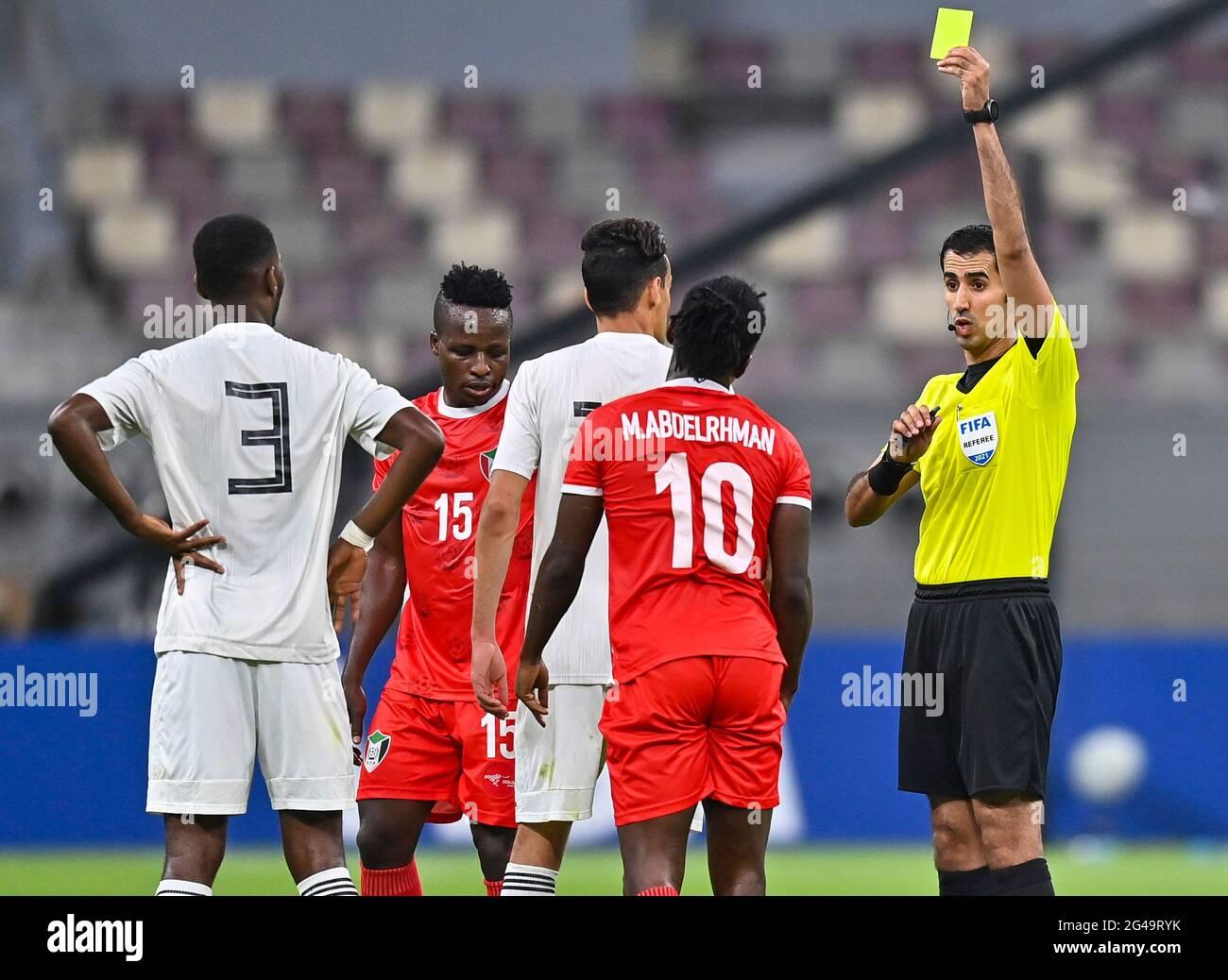 Doha, Qatar. 19 juin 2021. Saoud Al Adba, arbitre qatari (1er R), présente une carte jaune à Mohamed Abdelrhman (2e R) du Soudan lors du match de qualification de la coupe arabe de la FIFA au Qatar 2021 à Doha, Qatar, le 19 juin 2021. Credit: Nikku /Xinhua/Alay Live News Banque D'Images