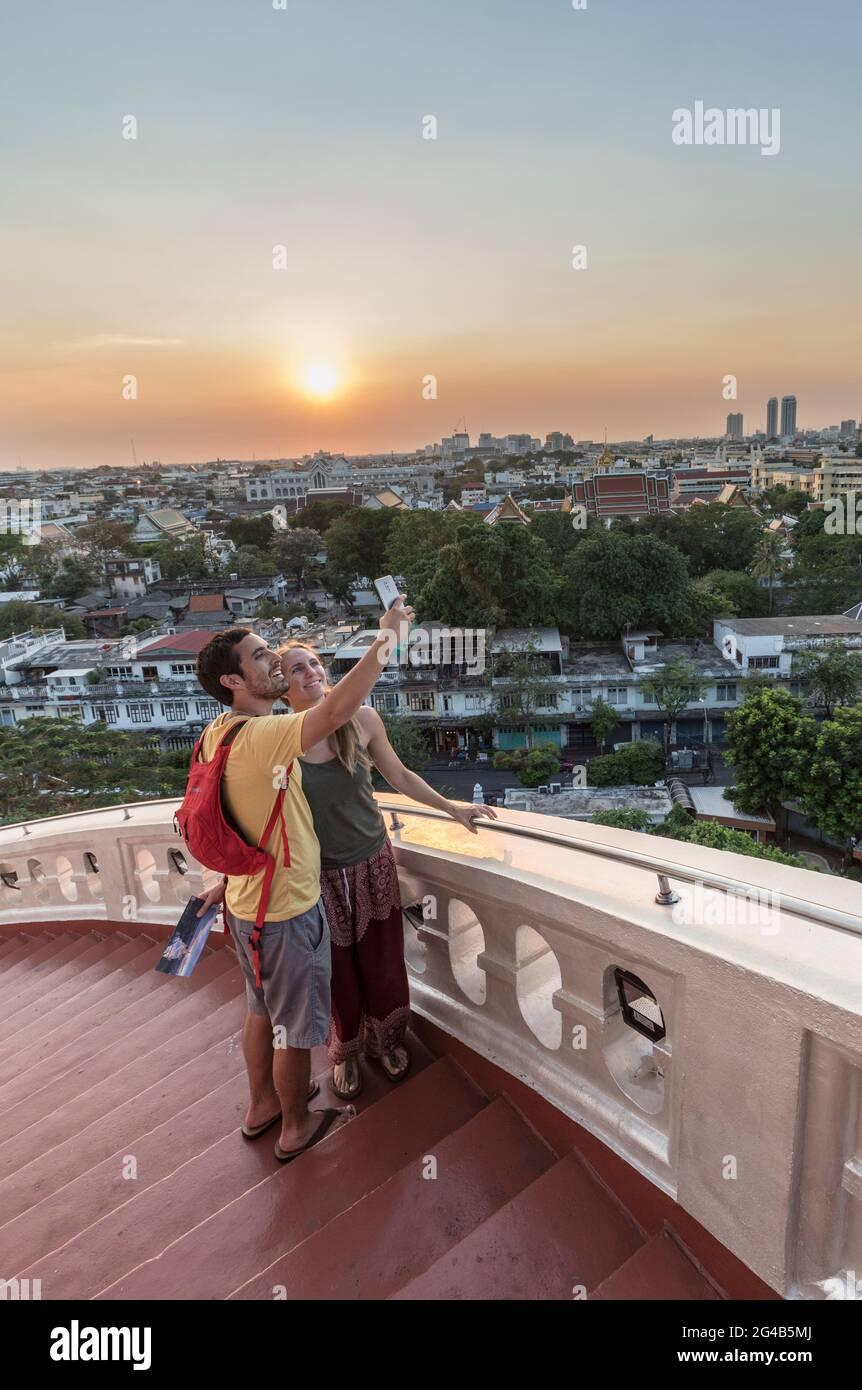 Couple prenant un selfie au coucher du soleil à Wat Saket, Golden Mountain, Temple de Srakesa, Bangkok, Thaïlande Banque D'Images