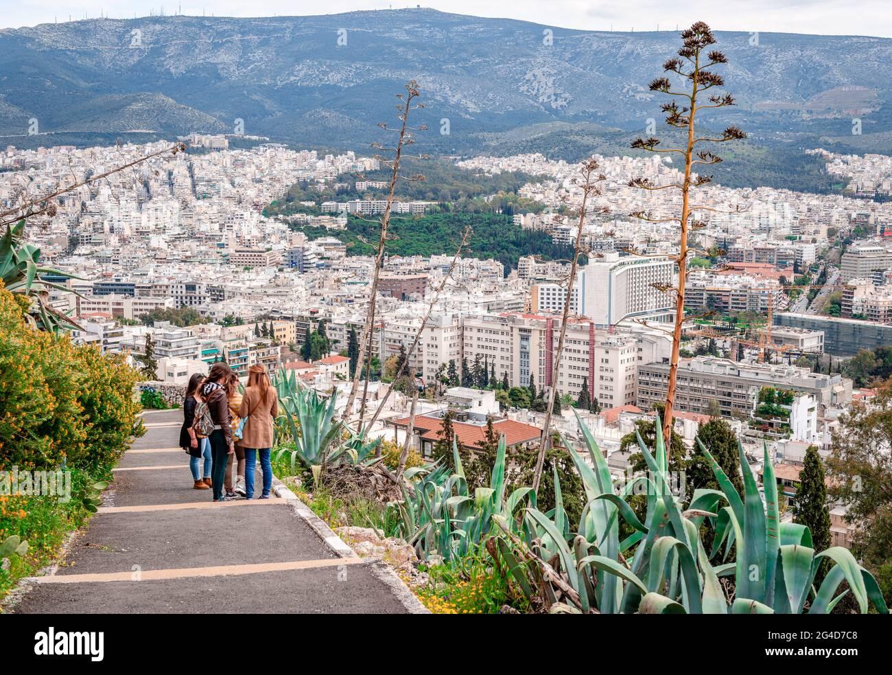 Athènes, Grèce - avril 4 2015 : les jeunes filles profitent de la vue depuis le sentier qui mène au mont Lycabette. Athènes et le mont Hymettus sont dans le backgrou Banque D'Images