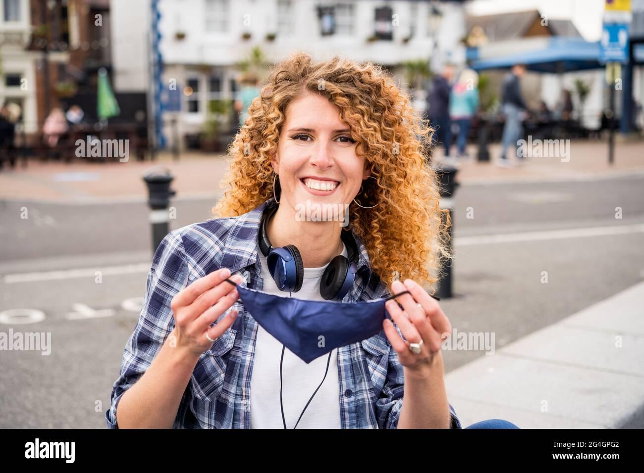 Une jeune femme caucasienne heureuse prend un masque protecteur couvrant le visage à l'extérieur sur fond de ville européenne. La pandémie Covid-19 est terminée Banque D'Images
