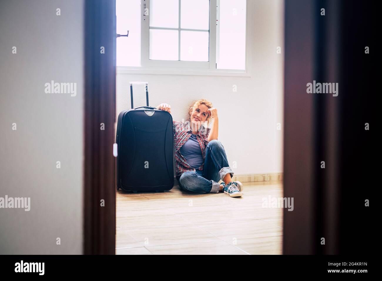 Une femme s'assoit seule à l'intérieur de la maison vide avec des bagages - nouvelle maison hypothécaire acheteurs personnes concept - immobilier femme dame relaxant intérieur Banque D'Images