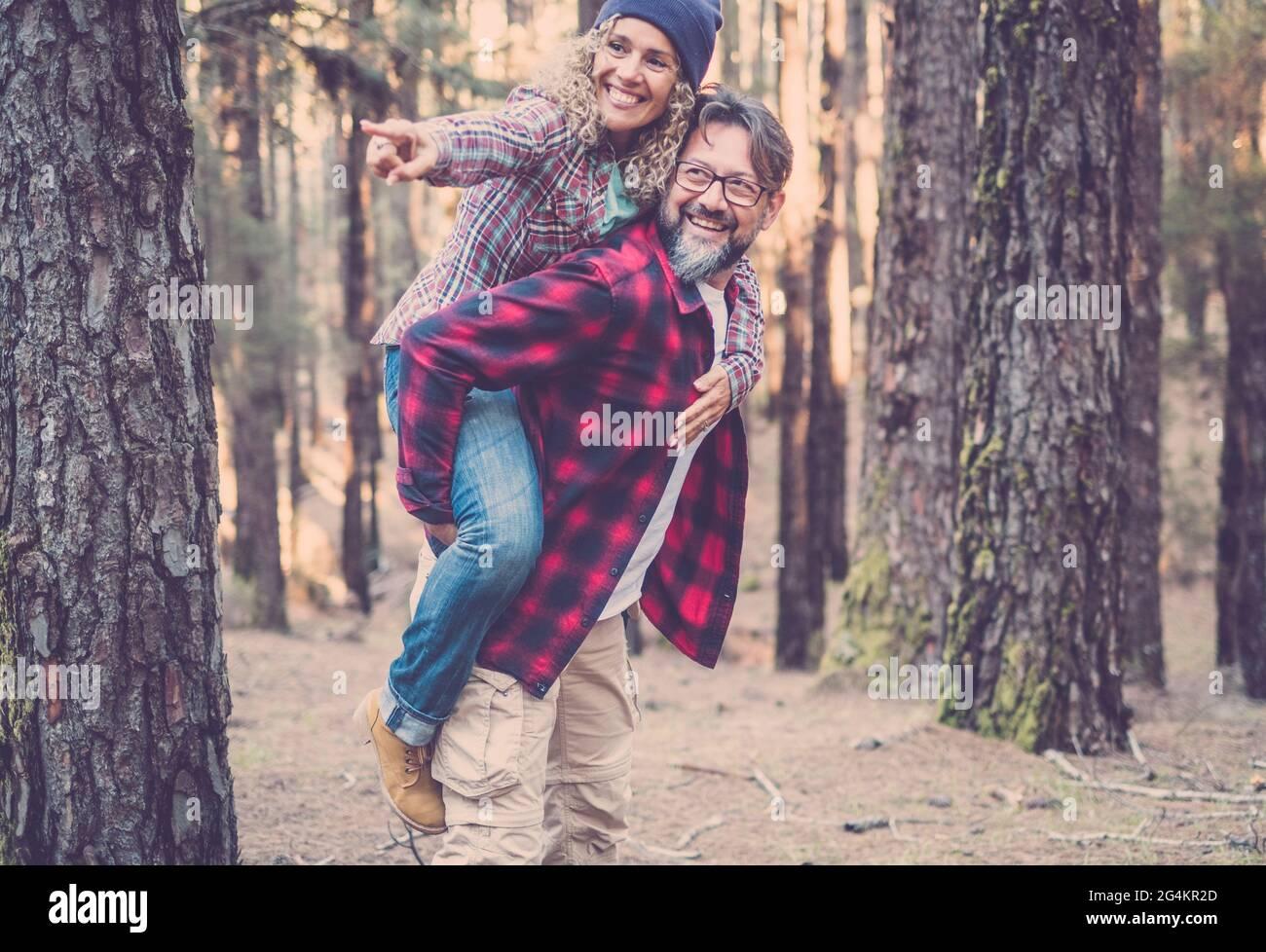 Joyeux et amusant couple caucasien ayant le piggyback tout en marchant sur le sentier dans les bois. Concept d'aventure dans la nature - jeune homme et femme adulte enjo Banque D'Images