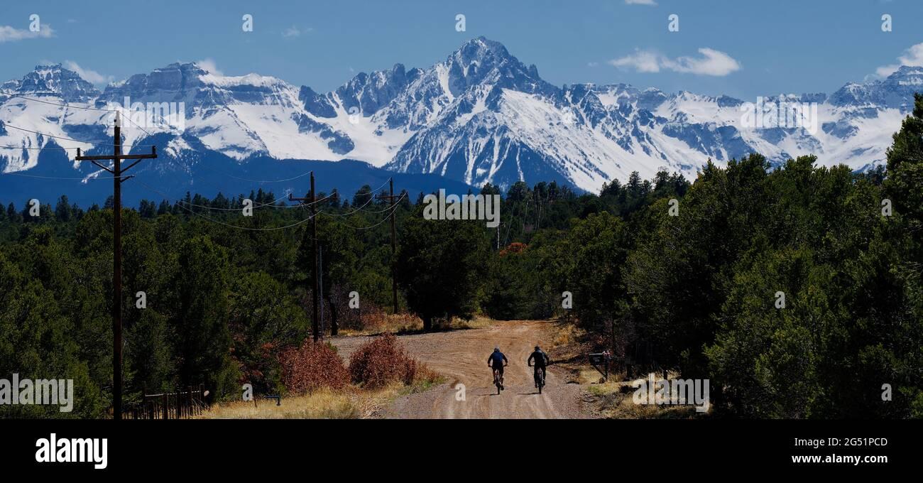 Deux motards longeant une route de terre avec des montagnes en arrière-plan, Colorado, États-Unis Banque D'Images