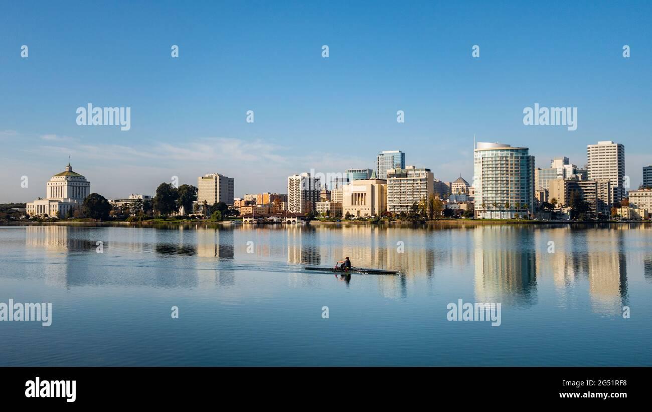 Homme ramer en bateau sur le lac Merritt avec les gratte-ciel d'Oakland en arrière-plan, Californie, États-Unis Banque D'Images