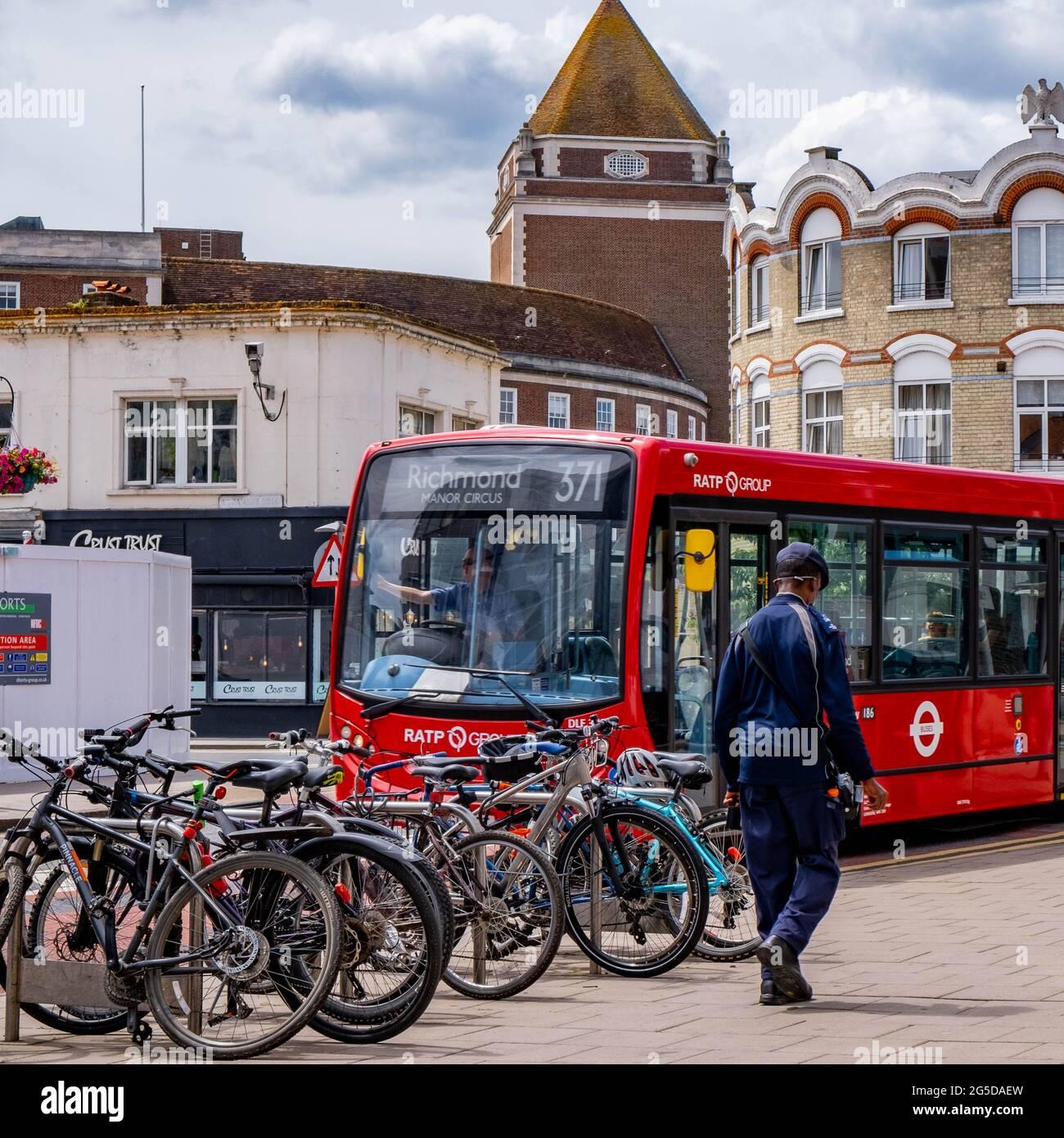 Kingston London, Royaume-Uni, juin 26 2021, Homme passant devant UNE rangée de bicyclettes garées et UN bus de transport public à un seul Decker Red Banque D'Images