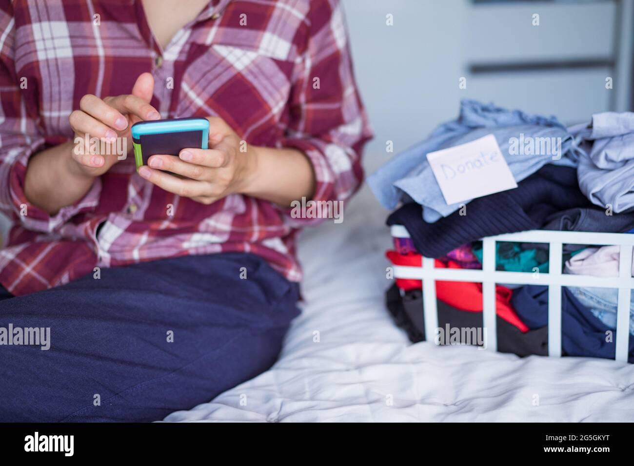 Gros plan femme utilisant son smartphone pour trouver des endroits où donner ses vêtements. Débrayer les vêtements, trier et nettoyer. Consommateur conscient Banque D'Images