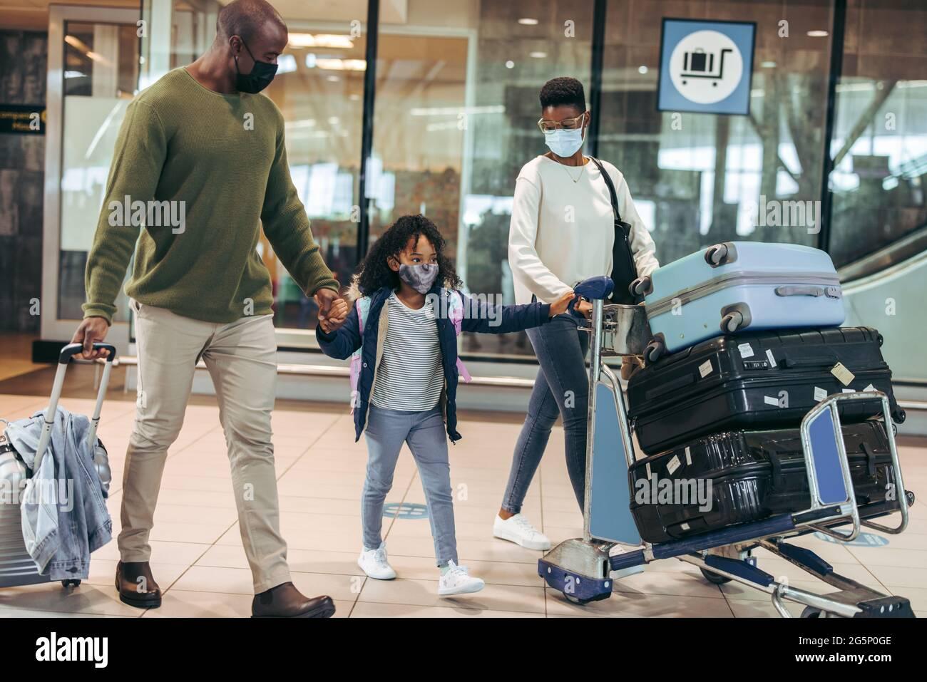 Homme et femme avec une jeune fille voyageant pendant une pandémie à l'aéroport. Famille africaine de trois personnes marchant au terminal de l'aéroport portant des masques. Banque D'Images
