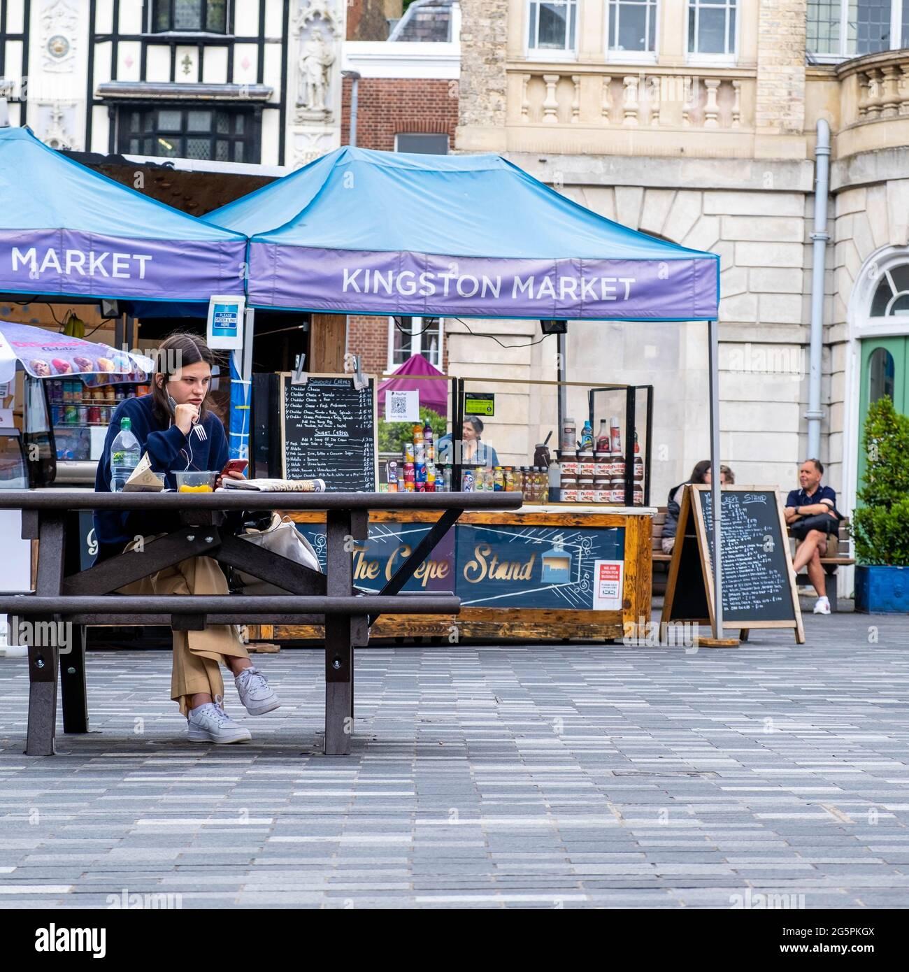 Kingston Londres UK, juin 29 2021, jeune femme assise seule à l'extérieur sur un banc en bois manger UN repas ou un déjeuner à emporter Banque D'Images