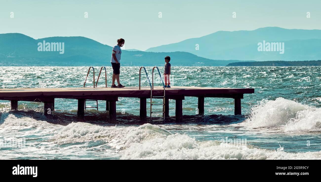 Urla, İzmir, Turquie - juin 2021 : un père parle à son fils sur un ponton en bois au-dessus de la mer à Urla, İzmir, Turquie. Banque D'Images