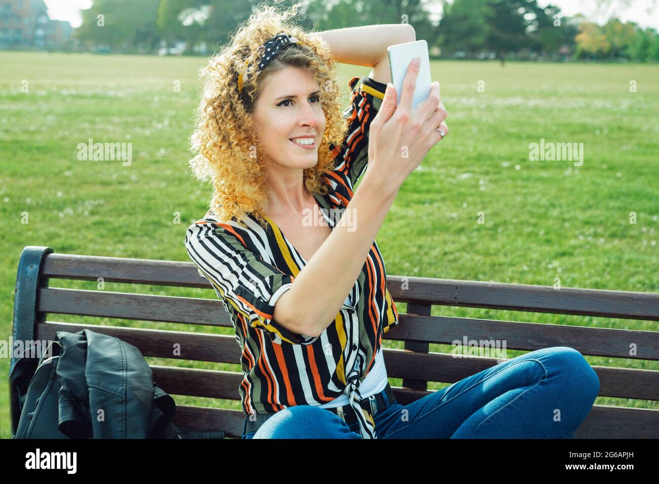 Une femme qui fait des photos de selfie sur un téléphone portable. Élégante femme souriante en chemise multicolore à rayures, posant sur le fond de la loi verte Banque D'Images