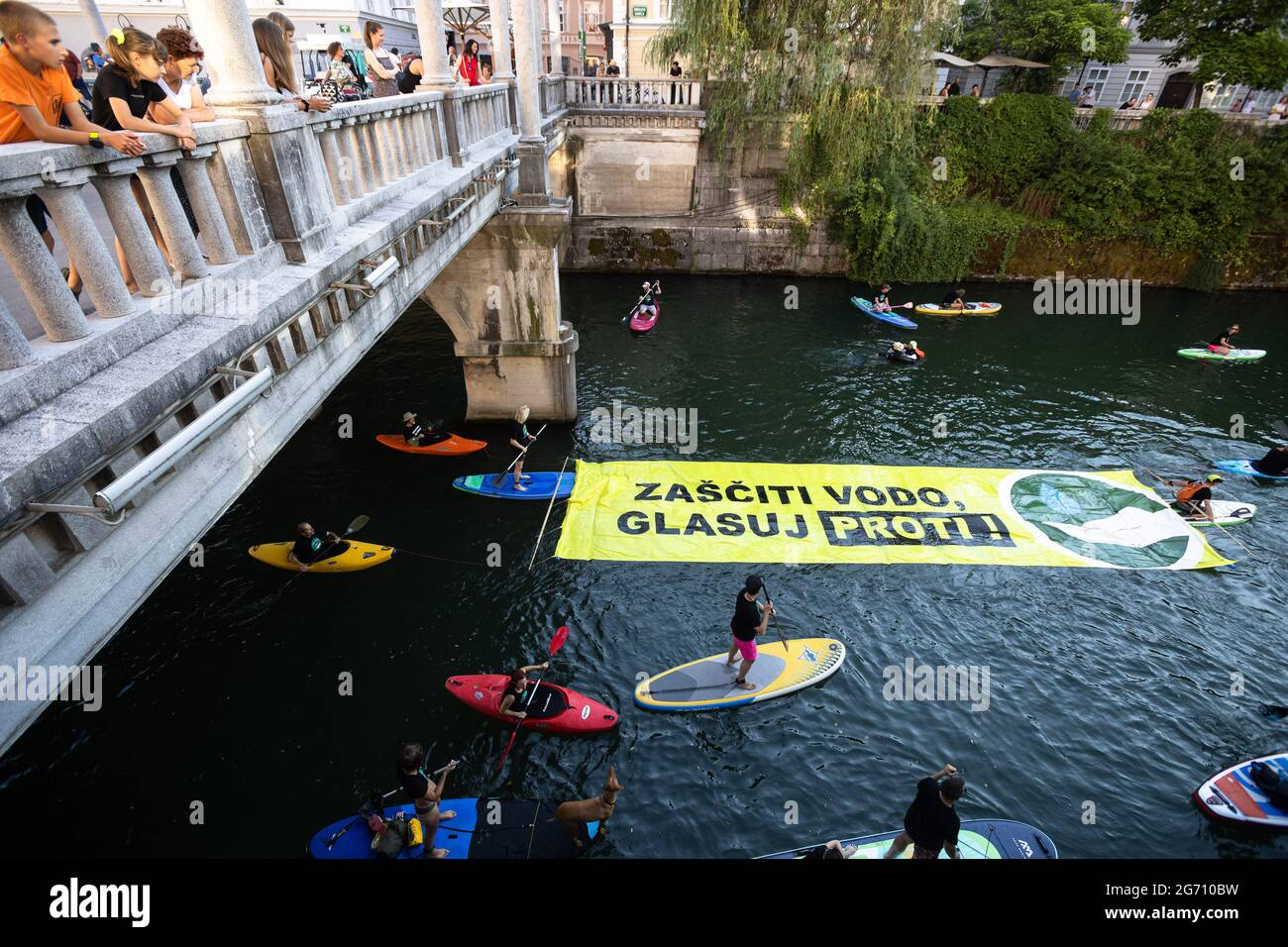 """Ljubljana, Slovénie. 09e juillet 2021. Les manifestants sur des planches à pédales, des kayaks et des canoës sur la rivière Ljubljana tirent une grande bannière qui dit """"protéger l'eau. Votez non ! » Pendant la manifestation, les manifestations antigouvernementales de vendredi contre les modifications proposées par le gouvernement à la loi sur l'eau ont continué d'encourager le public à voter contre la loi lors d'un référendum qui a lieu le 11 juillet. (Photo de Luka Dakskobler/SOPA Images/Sipa USA) crédit: SIPA USA/Alay Live News Banque D'Images"""