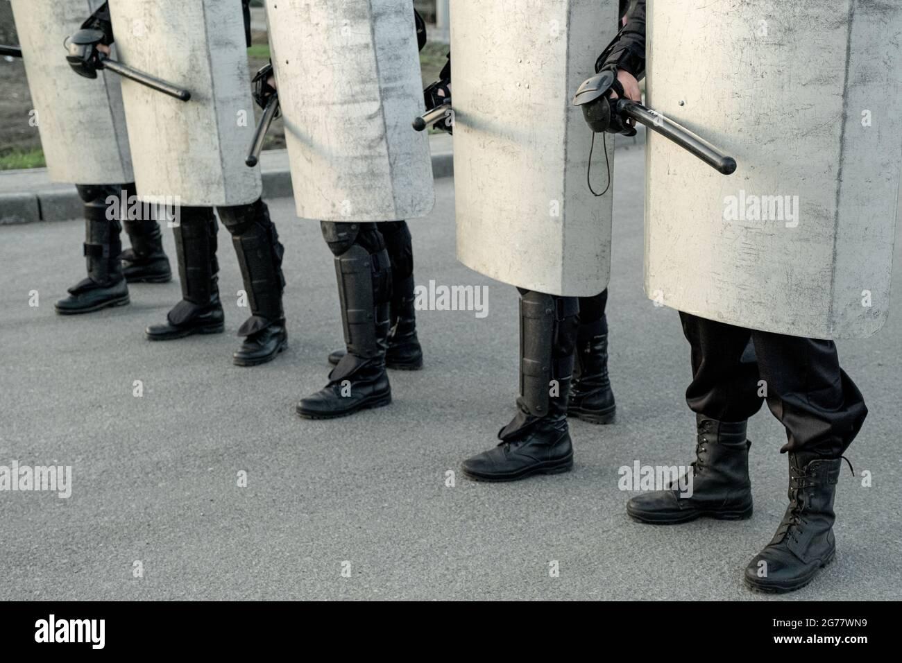 Groupe de forces de police se déplaçant avec des matraques dans la rue tout en effectuant une action coordonnée contre les manifestants Banque D'Images
