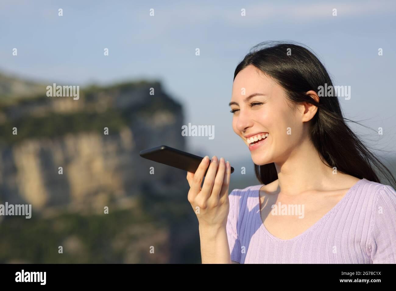 Bonne femme asiatique souriant en utilisant la reconnaissance vocale sur téléphone mobile dans la nature Banque D'Images