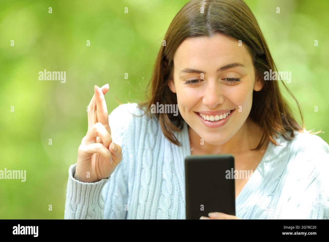 Une femme pleine d'espoir croisant ses doigts pour vérifier son smartphone dans un parc vert Banque D'Images