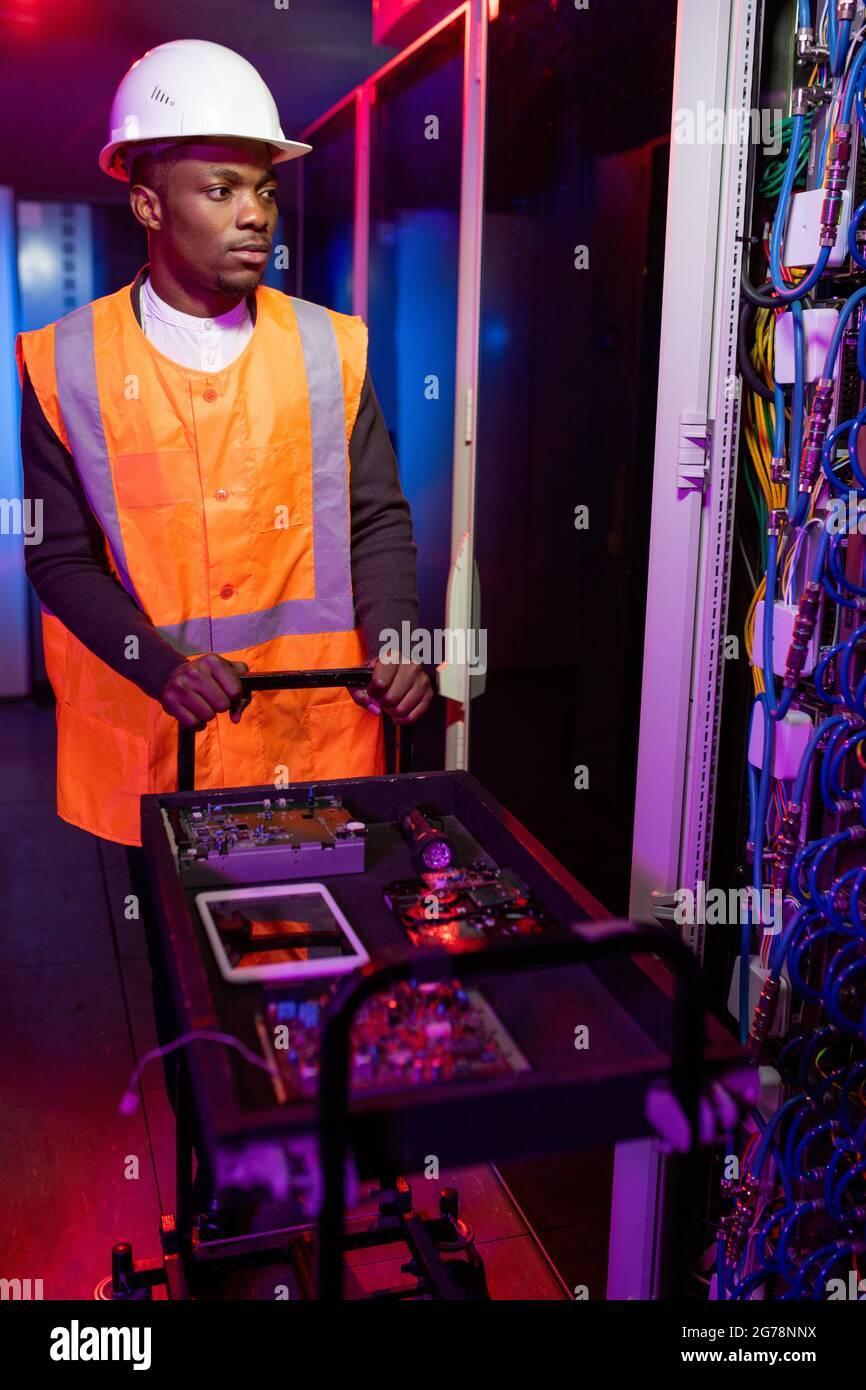 Jeune spécialiste sérieux de la réparation de serveur noir dans le chariot de poussée de casque et de gilet avec micropuces et cartes de circuit dans le centre de données en couleur néon Banque D'Images