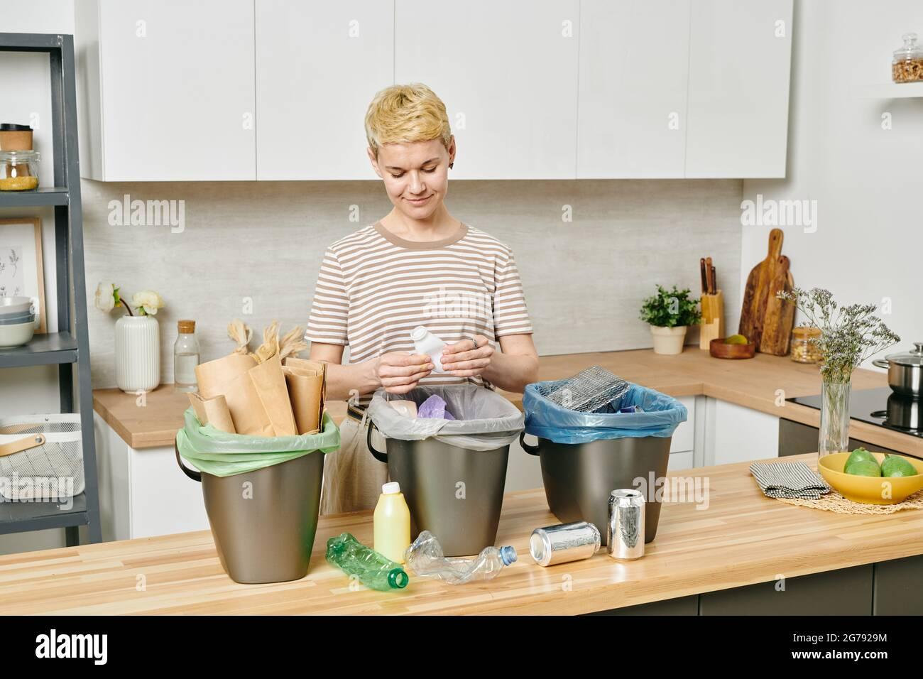 Jolie femme triant différents types de déchets dans trois bacs Banque D'Images