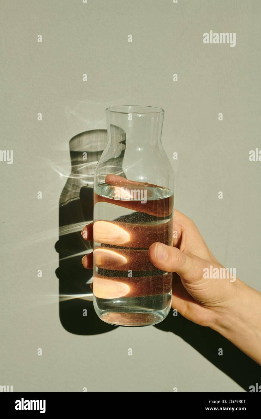 Main de jeune femme tenant une bouteille ouverte d'eau pure isolée Banque D'Images