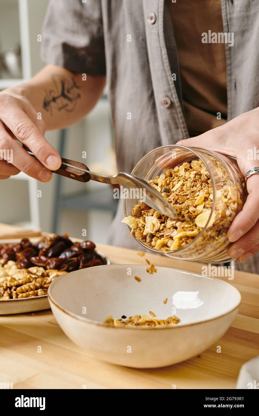 Mains de la femme mettant un peu de muesli dans le bol tout en faisant le petit déjeuner Banque D'Images