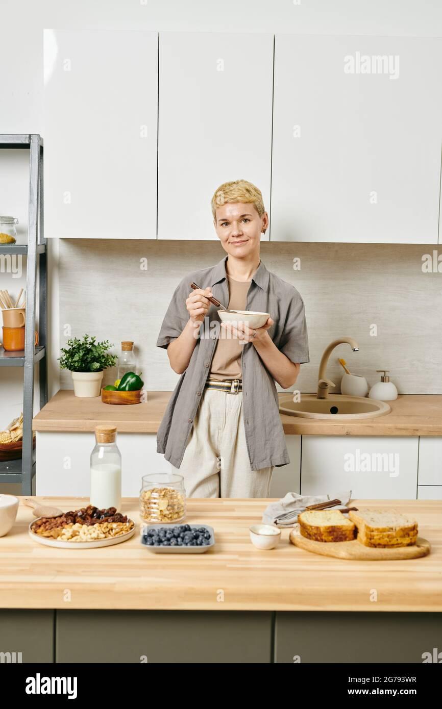 Jeune femme en bonne santé prenant le petit déjeuner devant la table de cuisine Banque D'Images