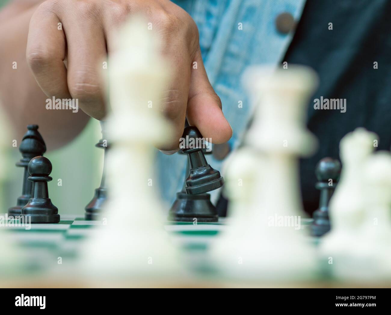 Jeu d'échecs sur un plateau vert, une main tient un pion noir Banque D'Images