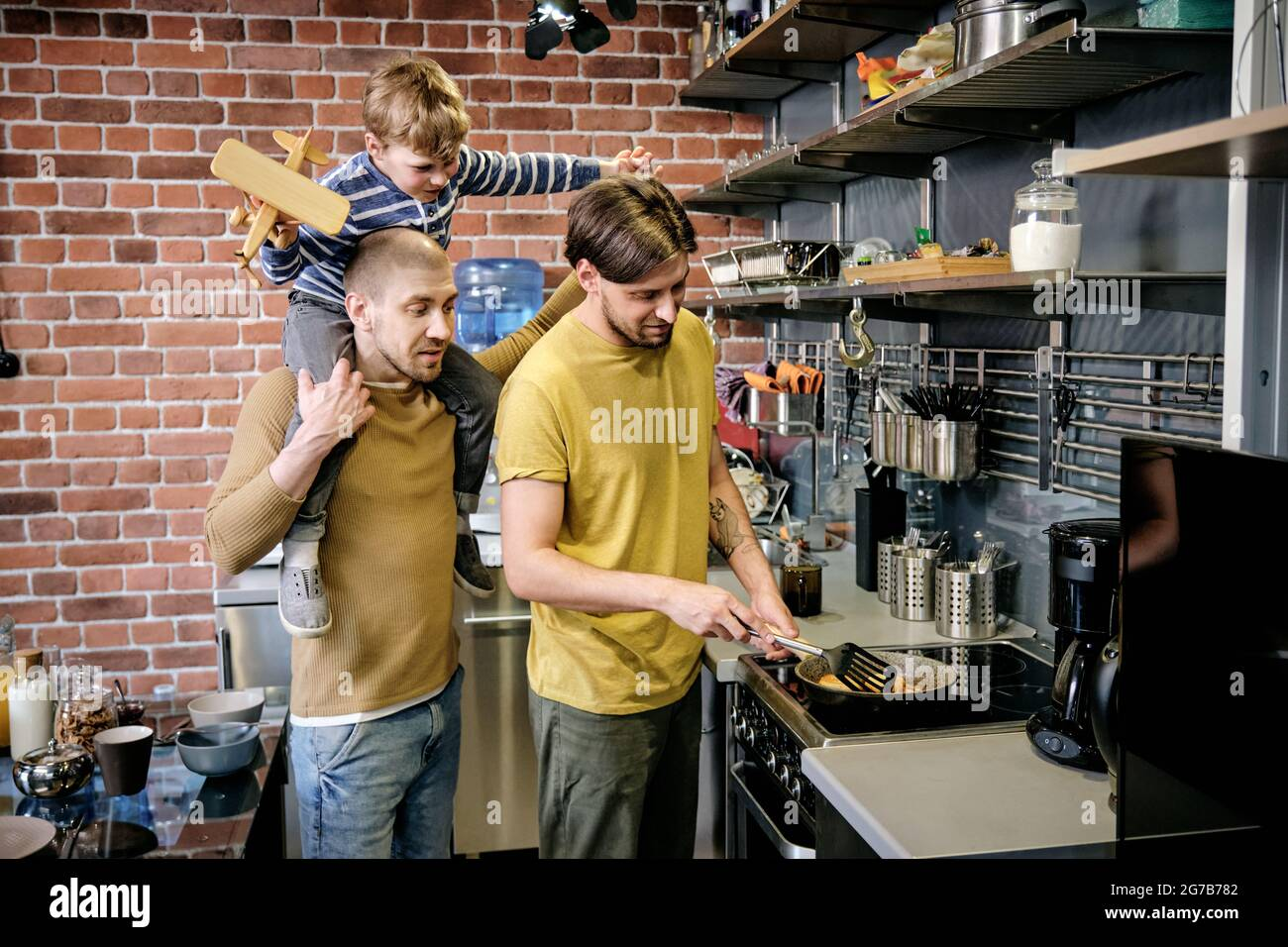 Jeune homme gay cuisant le petit-déjeuner sur la cuisinière dans la cuisine quand son mari donne le pigeyback tour à leur petit fils Banque D'Images