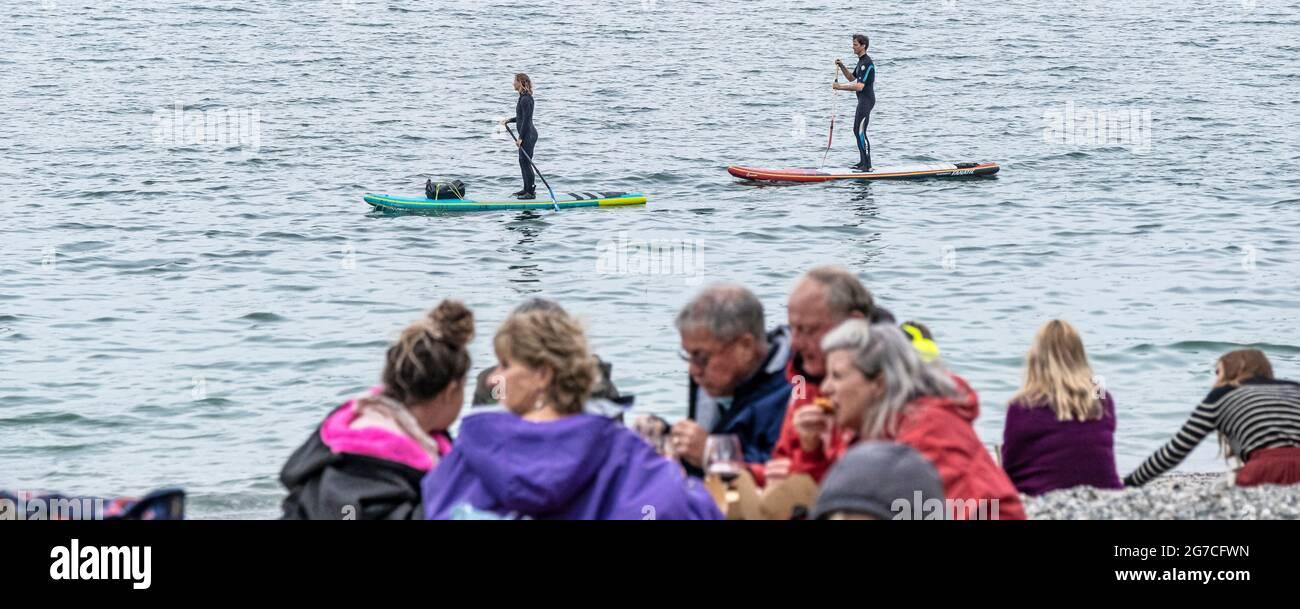 Les vacanciers sur les paddleboards Stand Up paddle long de la plage de Porthgwidden Cove sur la rivière Helford lors d'une journée froide à Cornwall. Banque D'Images