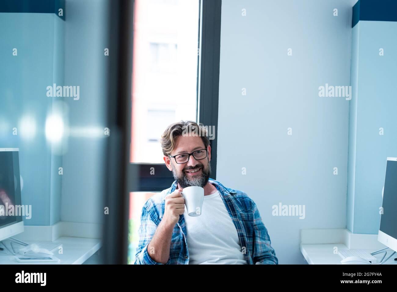Joyeux homme barbu adulte assis au bureau sourire et profiter de pause de travail en ligne - les gens et le style de vie de travail - les couleurs bleues - beau mal mûr Banque D'Images