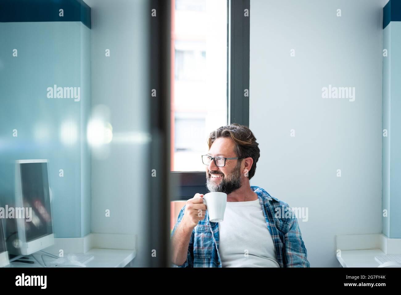 Portrait de l'homme heureux regardant à l'extérieur de la fenêtre et sourire en buvant un café à la maison ou au bureau - mâle caucasien adulte avec la barbe et les lunettes dans le travail br Banque D'Images