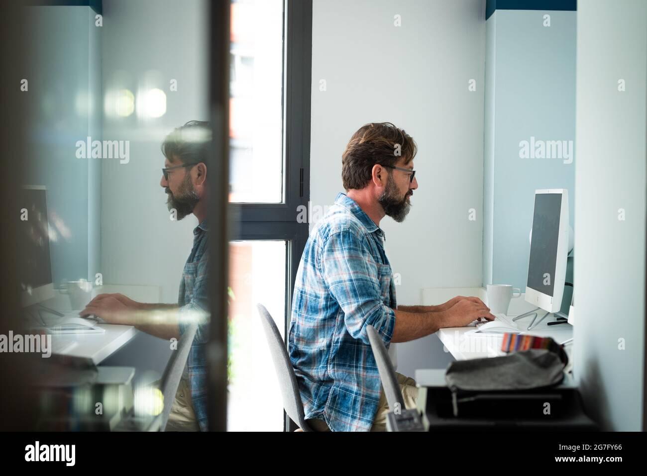 Caucasien freelance personnes homme assis au bureau dactylographiant sur ordinateur de bureau pour le travail en ligne Internet connecté style de vie - hipster adulte homme travaillant Banque D'Images