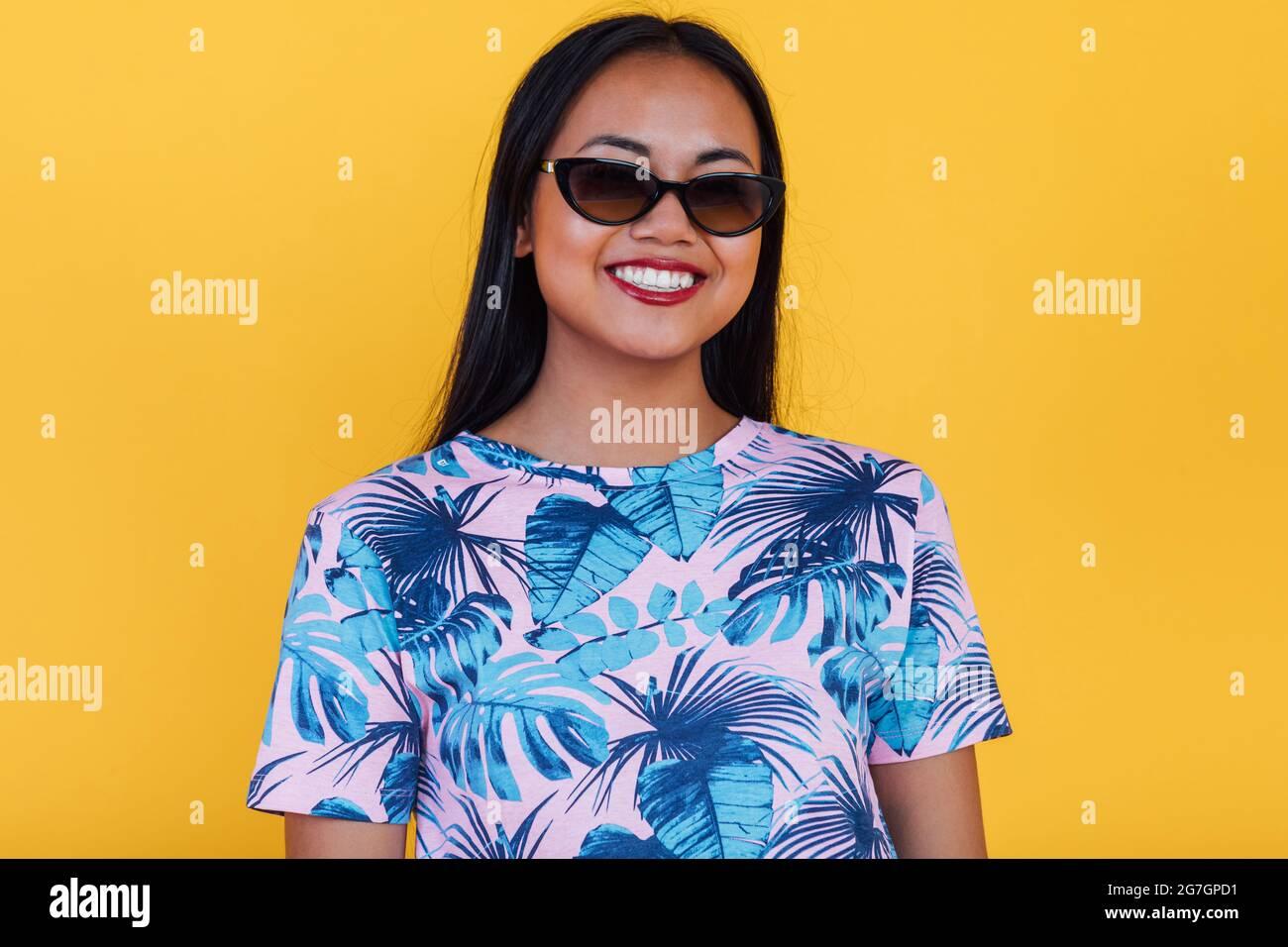 Happy Asian femme dans des lunettes de soleil élégantes et t-shirt avec imprimé feuilles tropicales regardant l'appareil photo sur fond jaune dans le studio Banque D'Images
