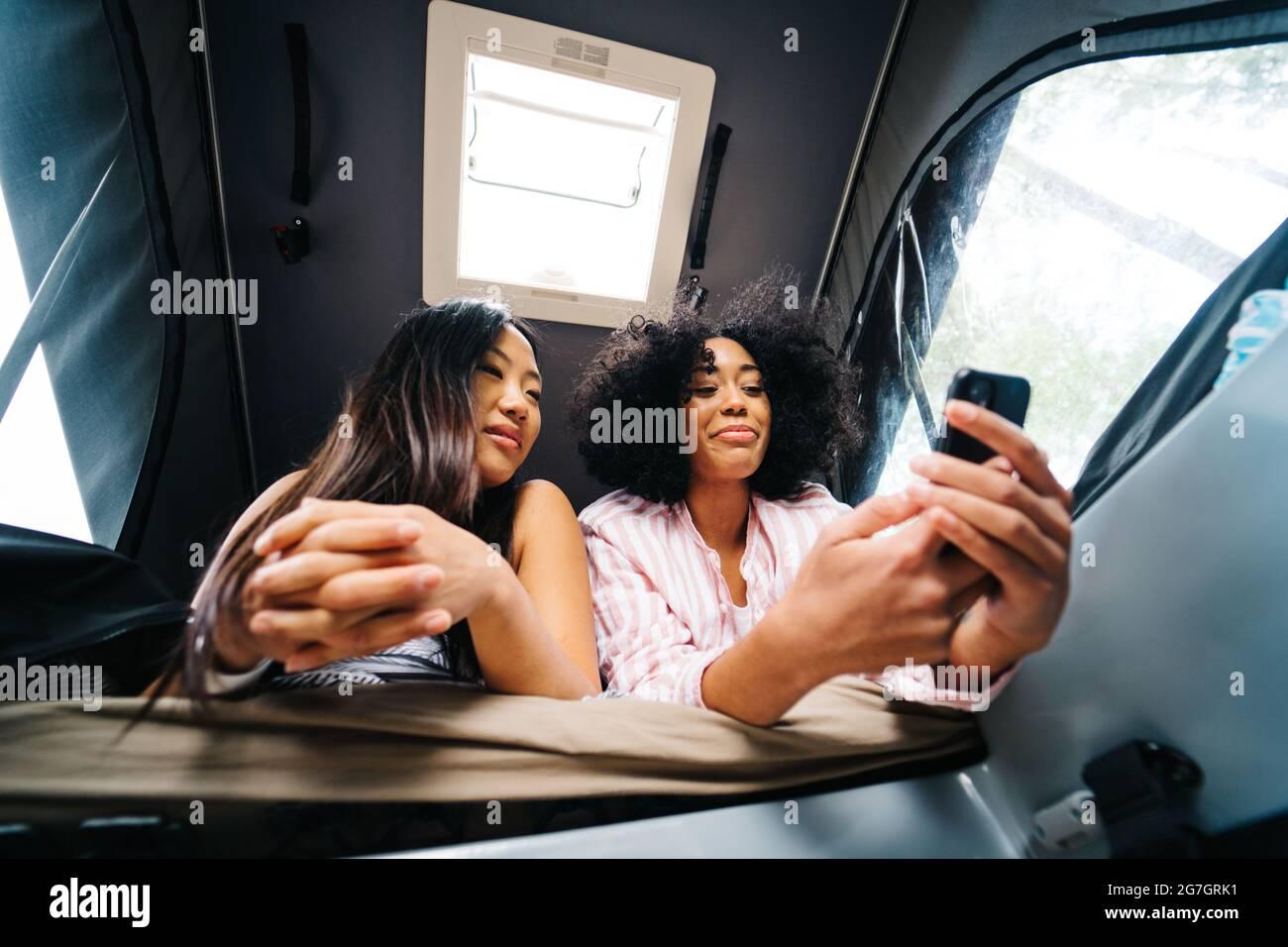 De dessous de jeunes amis asiatiques et afro-américains positifs naviguant sur le téléphone mobile tout en se reposant ensemble à l'intérieur de la camionnette de camping pendant l'été tr Banque D'Images
