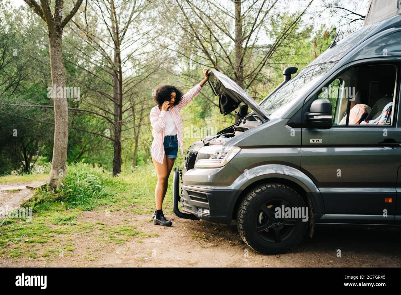 Jeune femme afro-américaine se tenant près d'une fourgonnette avec capot ouvert et parlant avec le service de réparation par téléphone portable tout en rencontrant des problèmes Banque D'Images