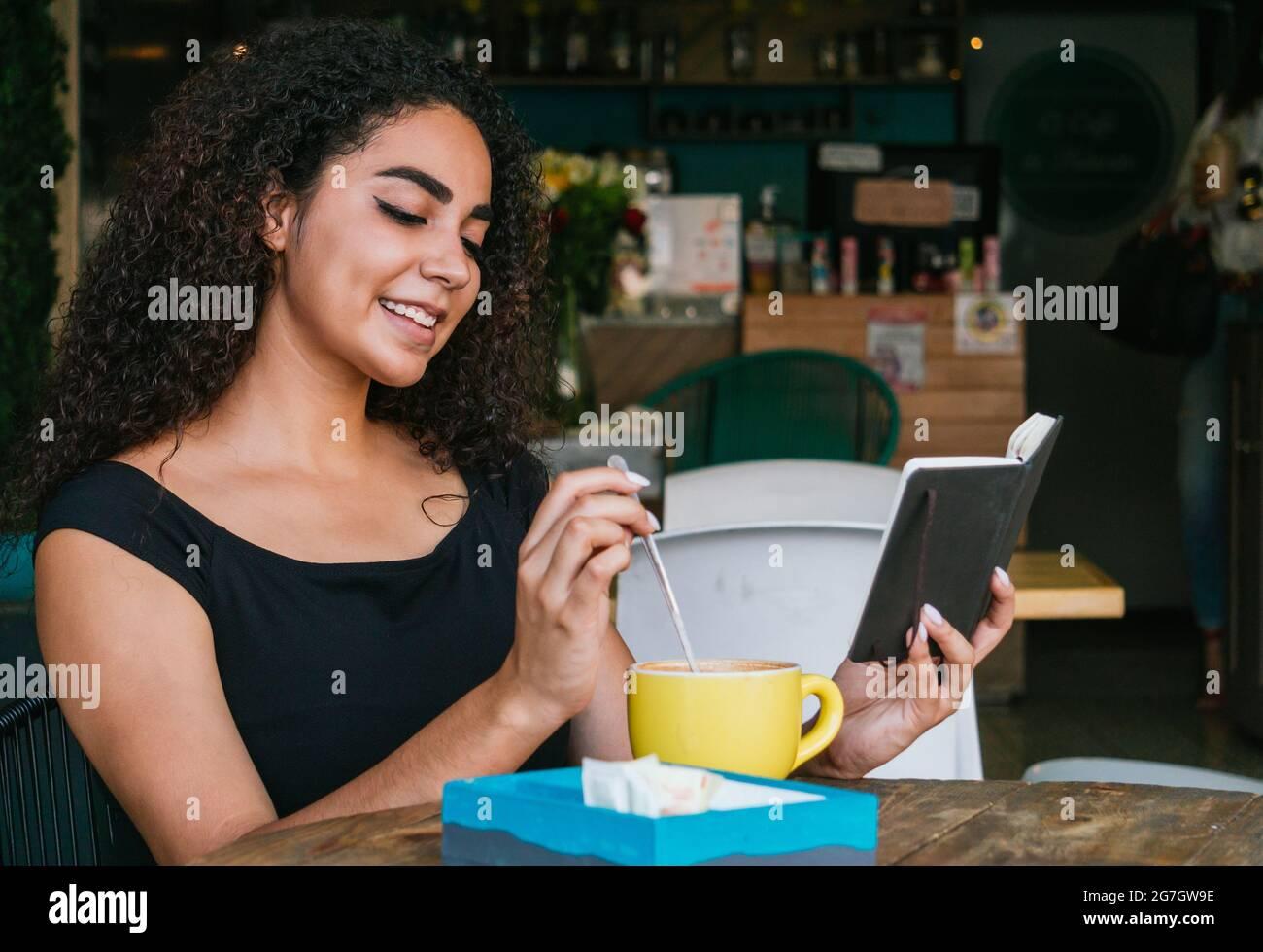Jeune femme hispanique souriante aux cheveux maurires, en train de se reposer à table avec une tasse de café sur la terrasse du café Banque D'Images