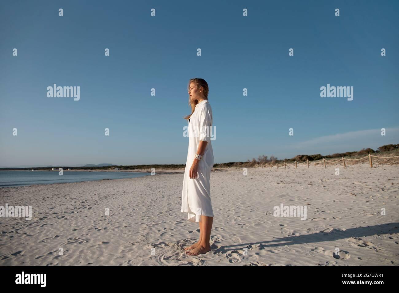 Femme blonde aux cheveux longs se tenant sur la plage en regardant au loin Banque D'Images