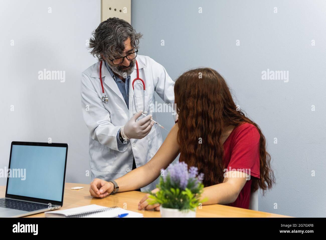 Homme âgé ayant fait une injection sur le bras de la patiente dans la salle médicale de l'hôpital Banque D'Images