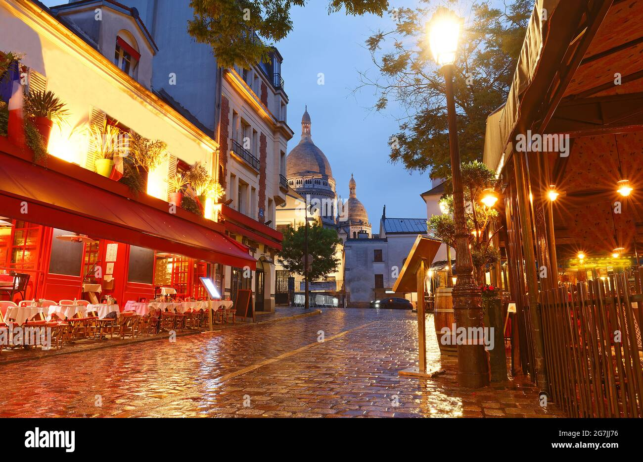 La place du Tertre avec des tables de café et le Sacré-coeur dans la nuit des pluies , quartier Montmartre à Paris, France Banque D'Images