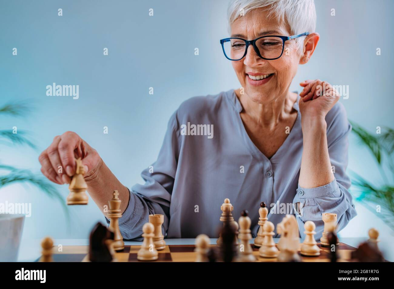 Senior woman playing chess Banque D'Images