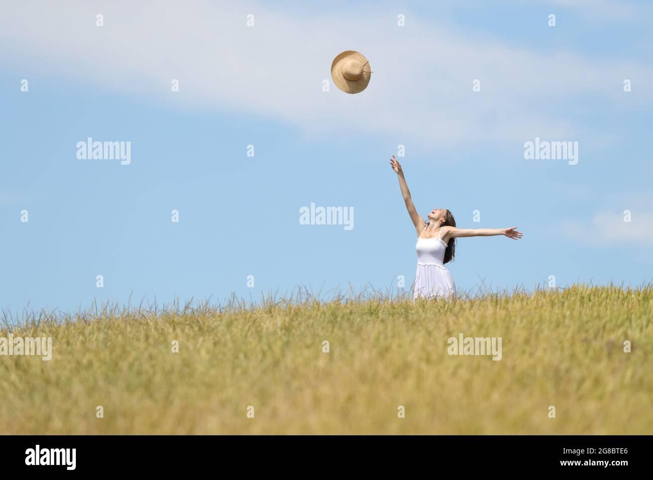 Femme excitée debout dans un champ de blé jetant le chapeau pamela à l'air Banque D'Images