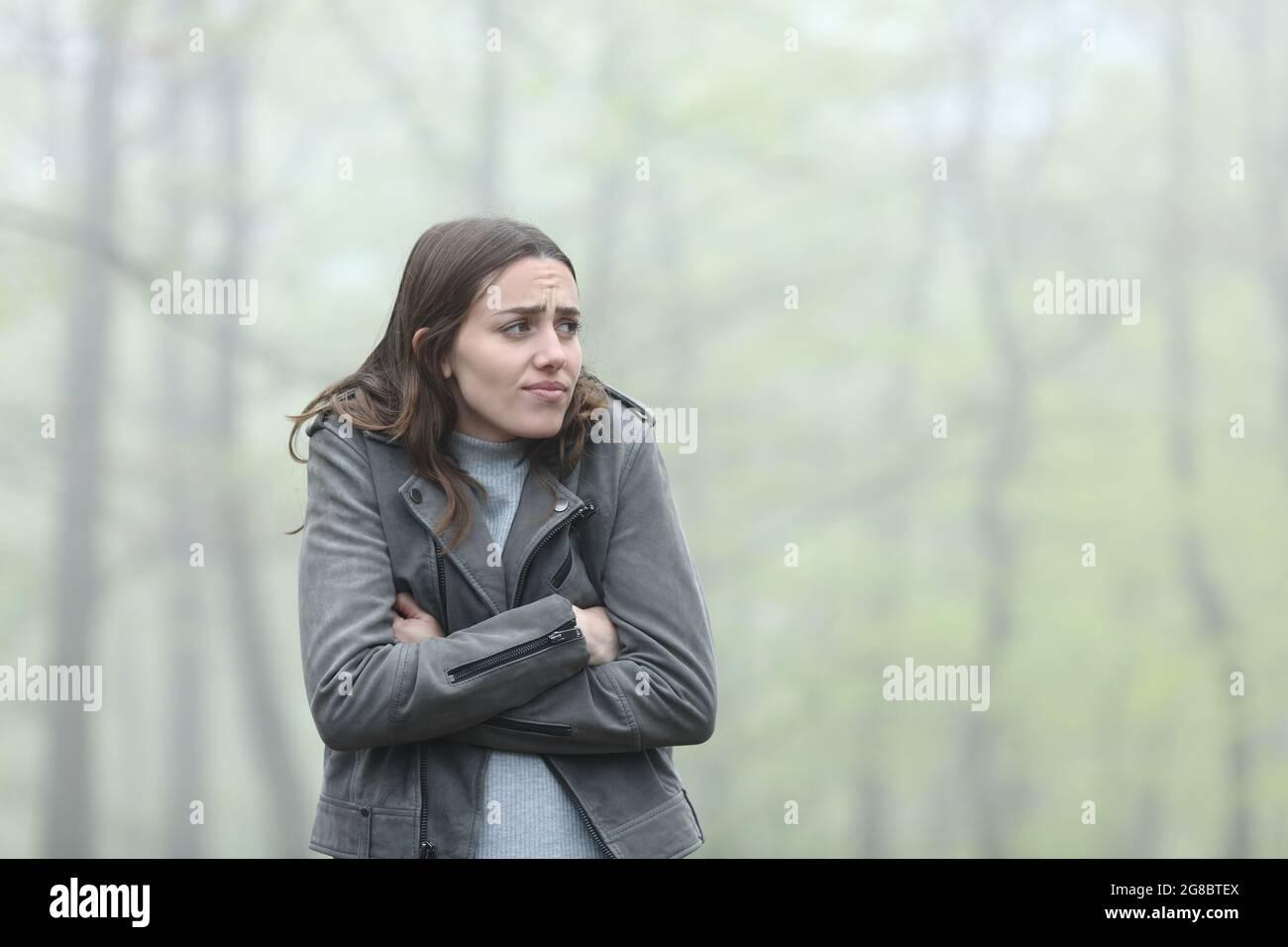 Une femme stressée se plaint de froid dans un parc brumeux Banque D'Images