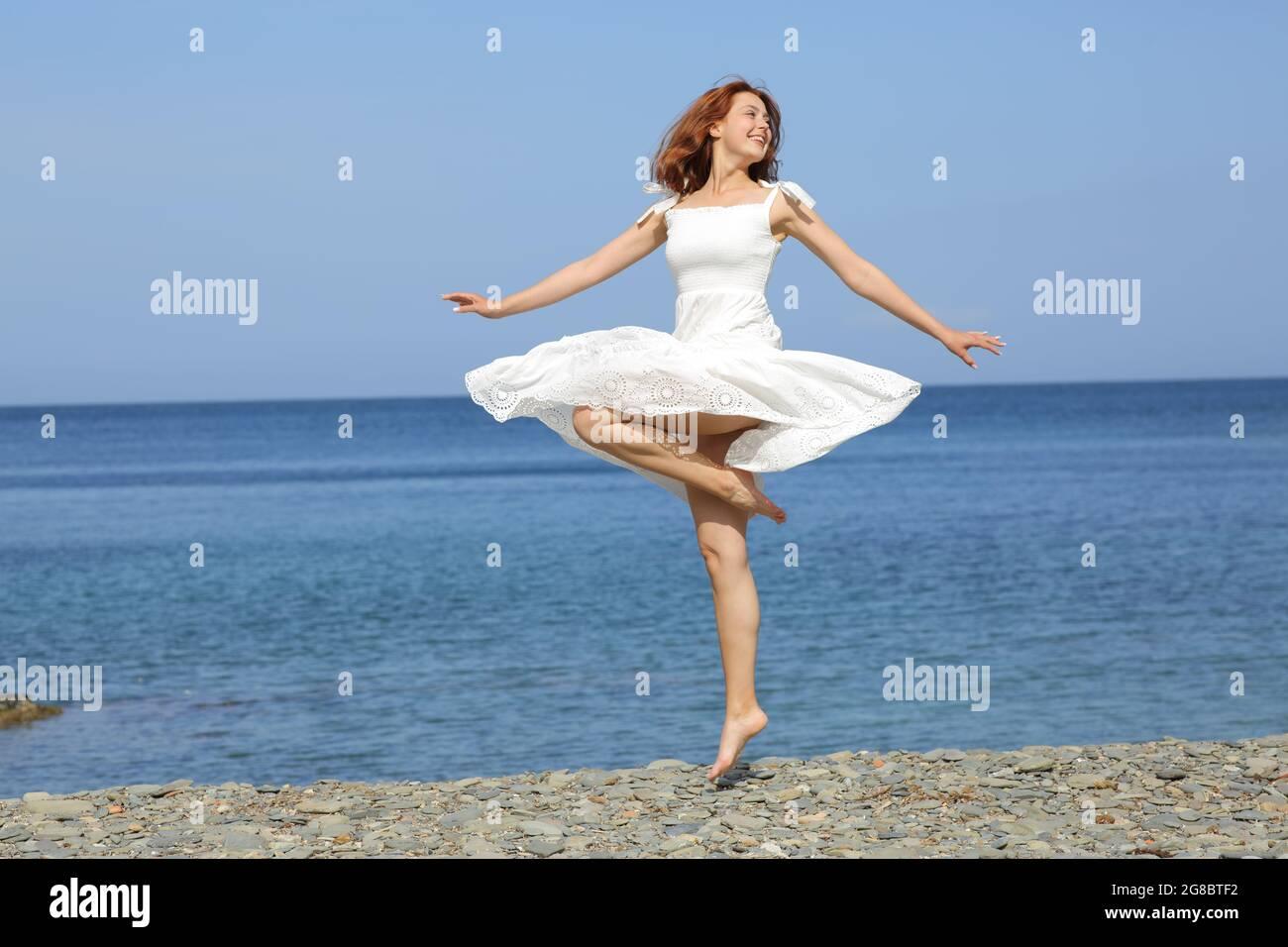 Bonne femme portant une robe blanche en tortillonnage sur la plage Banque D'Images