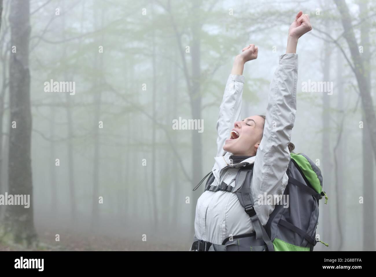 Un trekker excités qui célèbre ses réalisations dans une forêt brumeuse en vacances Banque D'Images