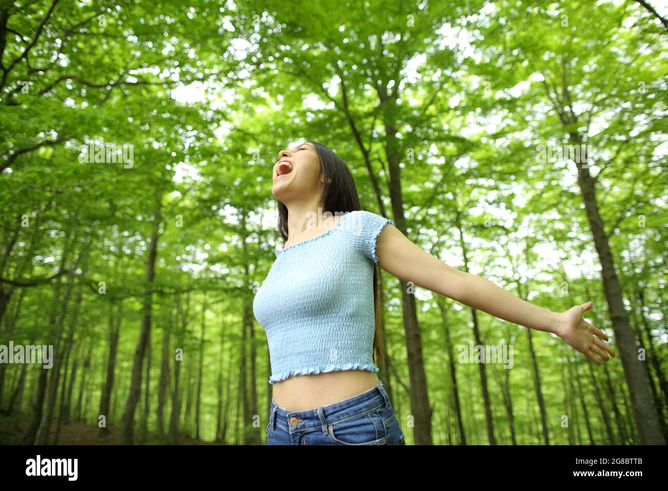 Femme asiatique excitée célébrant des vacances s'étirant les armes et hurlant dans une forêt verte Banque D'Images