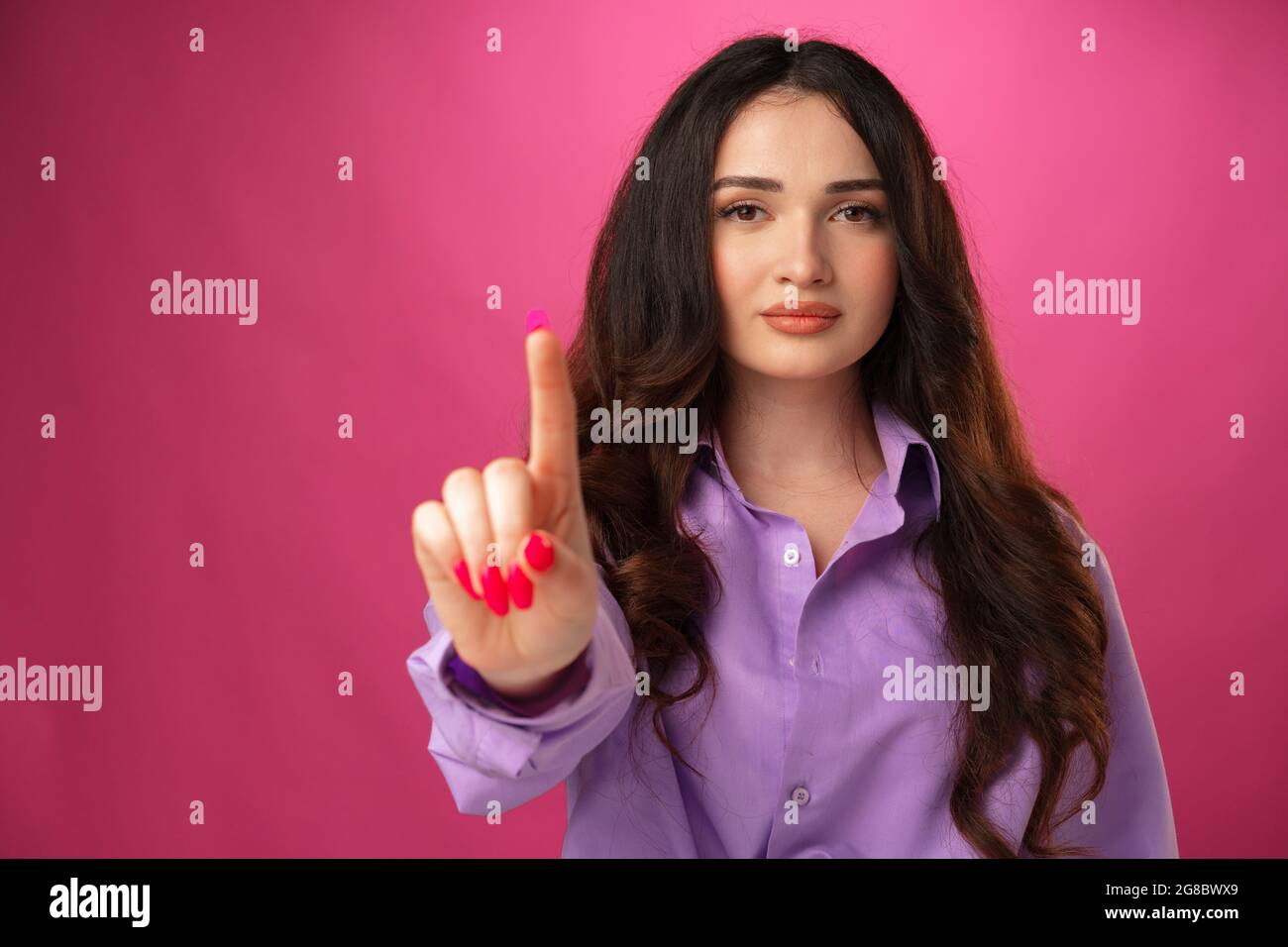 Jeune femme confiante montrant un geste d'arrêt, pointant le doigt Banque D'Images