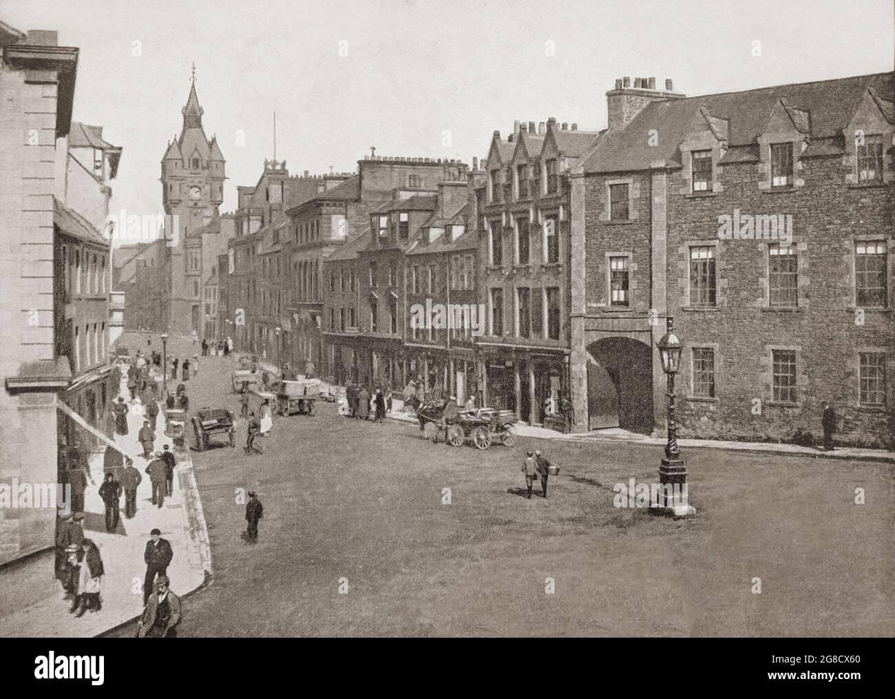Vue de la fin du XIXe siècle sur High Street à Hawick, ville aux frontières écossaises et comté historique de Roxburghshire, dans l'est du sud des Uplands. L'hôtel de ville de style écossais-baronial de Hawick est visible au bout de la rue, ainsi que ses nombreux bâtiments en grès avec toits en ardoise. Banque D'Images
