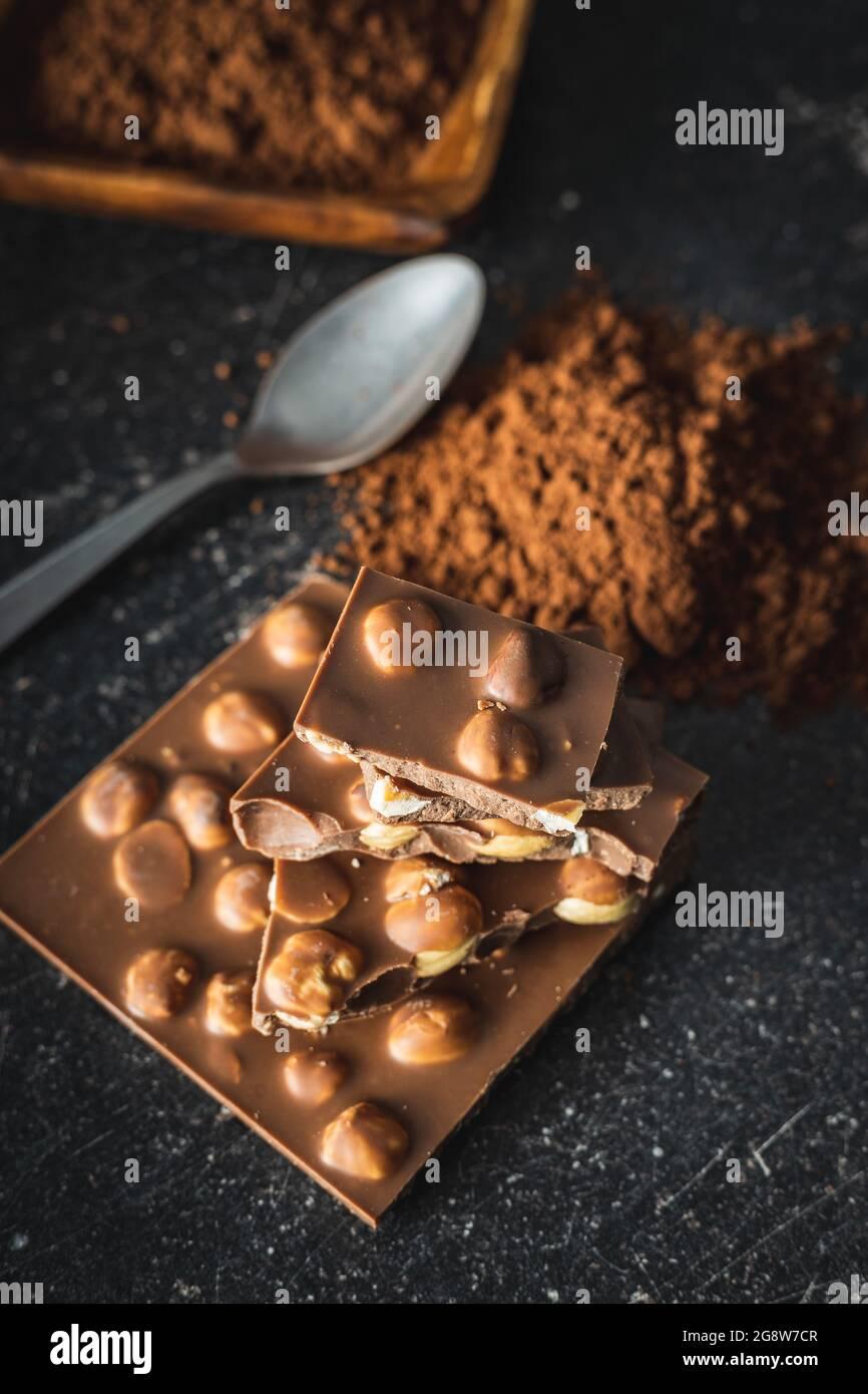 Chocolat à la noisette avec noisettes et poudre de cacao sur table noire. Banque D'Images