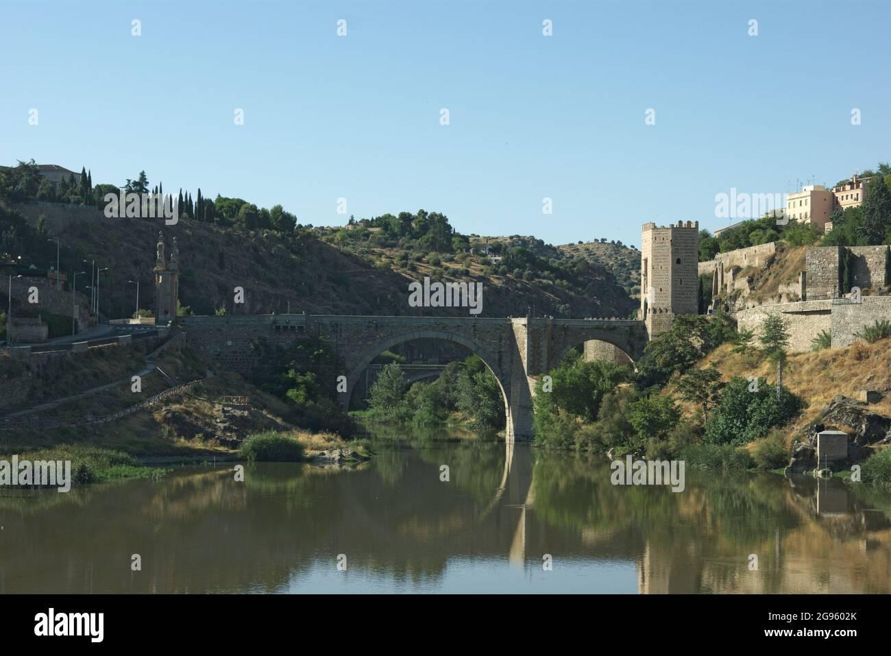 Vue sur le pont Alcantara à Tolède, Espagne. La forme élégante du pont se reflète sur les eaux fixes du Tage. Banque D'Images