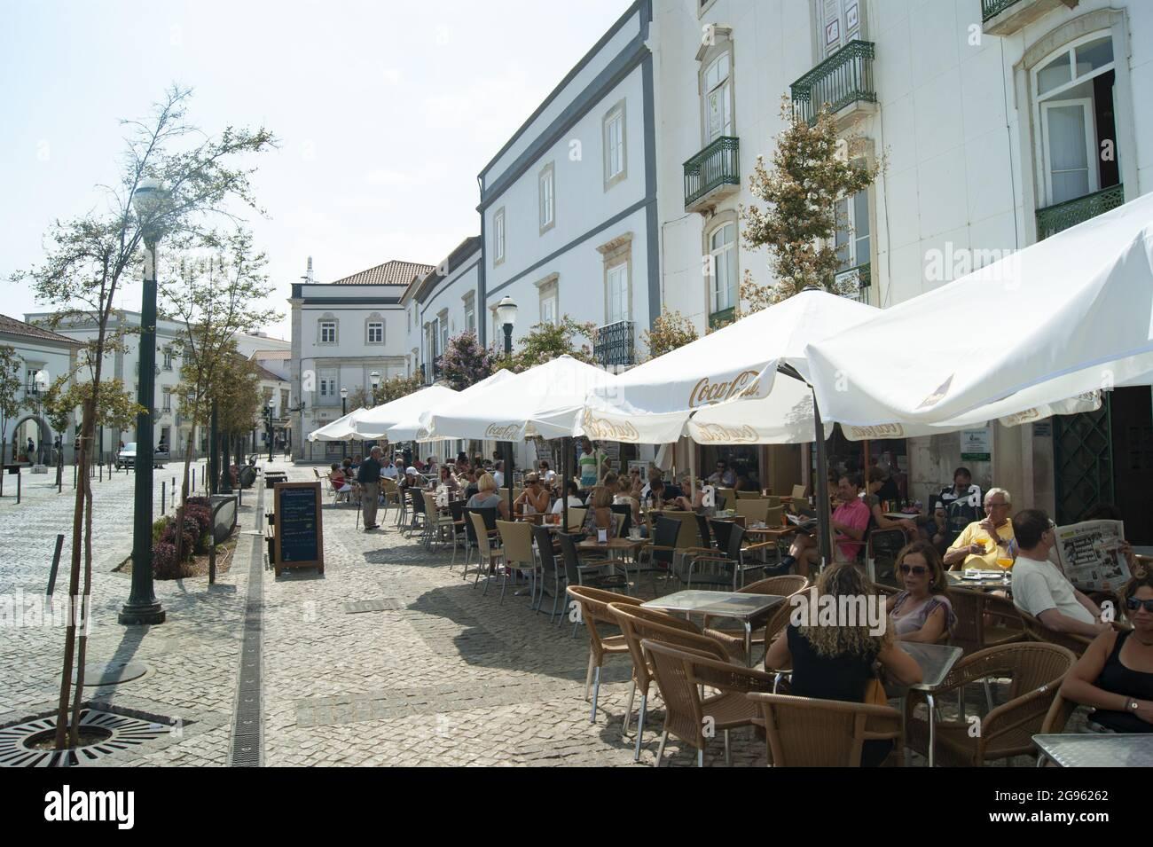 Tavira / Portugal / septembre 21 2012 : les vacanciers apprécient les boissons et la nourriture dans un café situé sur le trottoir au cœur de la vieille ville. Des parasols sont à votre disposition Banque D'Images