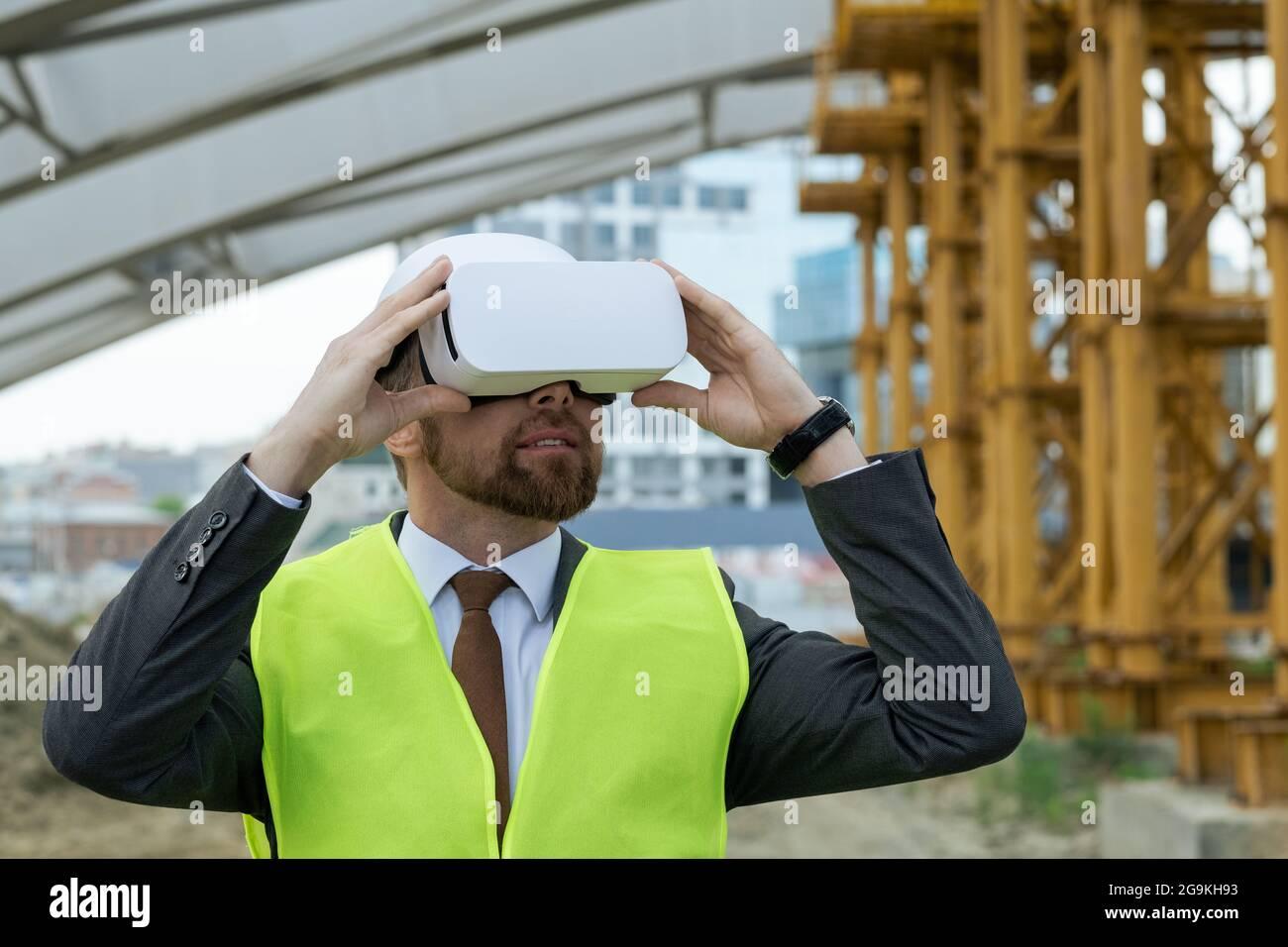 Ingénieur mature regardant le futur projet à travers les lunettes de réalité virtuelle en se tenant sur le chantier de construction Banque D'Images