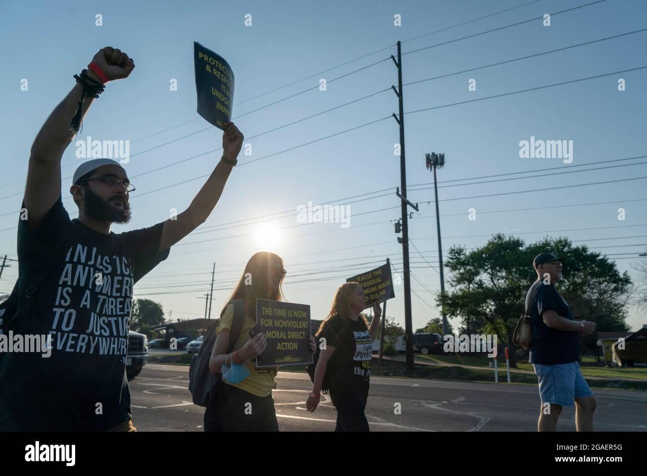 Austin, Texas USA, le 30 juillet 2021 : les militants des droits de vote marchent le long d'une voie de desserte autoroutière vers le capitole du Texas depuis le nord d'Austin le troisième jour d'un voyage de 30 miles protestant contre les efforts républicains pour supprimer les votes dans tout le pays et au Texas. Des changements de marcheurs se font échanger dans un effort pour lutter contre la chaleur oppressive du Texas. Crédit : Bob Daemmrich/Alay Live News Banque D'Images